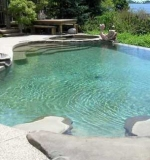 A – Freeform pool with vanishing edge overlooking the bay. Attached spa, custom walk-in stairs and sun shelf area.