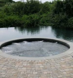 Beach entry pool with spa and vanishing edge.