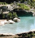 Beach entry pool with sunken boulders, hidden lagoon and waterfall.