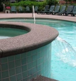 Commercial pool with cantilever aggregate deck and tiled spa.