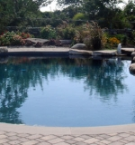 Paver deck with midnight stone finish. Natural boulder wall creates a lagoon look.