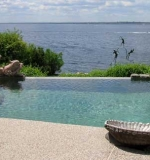Freeform pool with vanishing edge overlooking the bay. Attached spa, custom    walk-in stairs and sun shelf area.