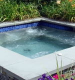 10' x 10' gunite spa with a stone veneer exterior with bluestone coping and automatic cover.