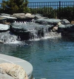 Natural boulders set on shelves below water level with 6' high cascading waterfall.